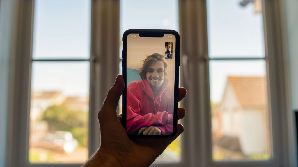 Man is holding a smartphone and having a videocall